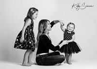 Black and white studio portrait mom dancing with baby girl and older sister laughing