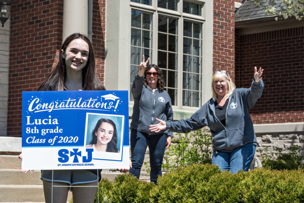 Two teachers surprising teen girl student with graduation lawn sign