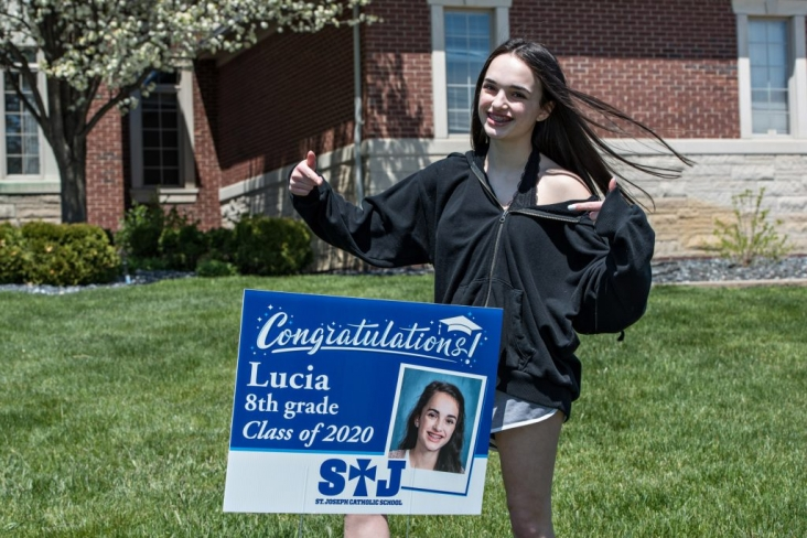 Teen girl smiling pointing at a graduation line sign in her yard