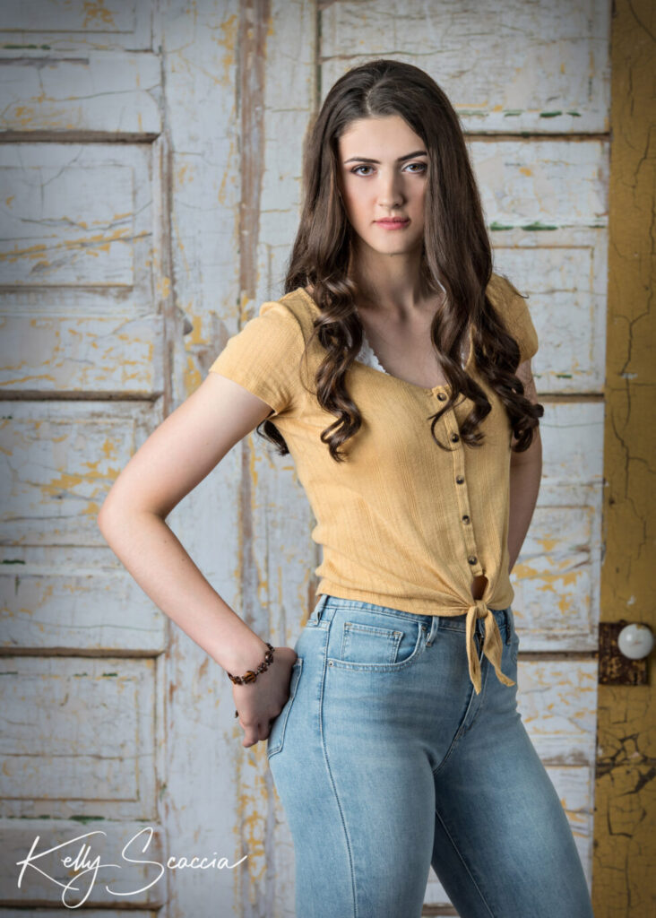 Tall girl with long hair studio portrait wearing jeans and yellow shirt with hands in back pockets while standing and looking straight at you with a serious expression