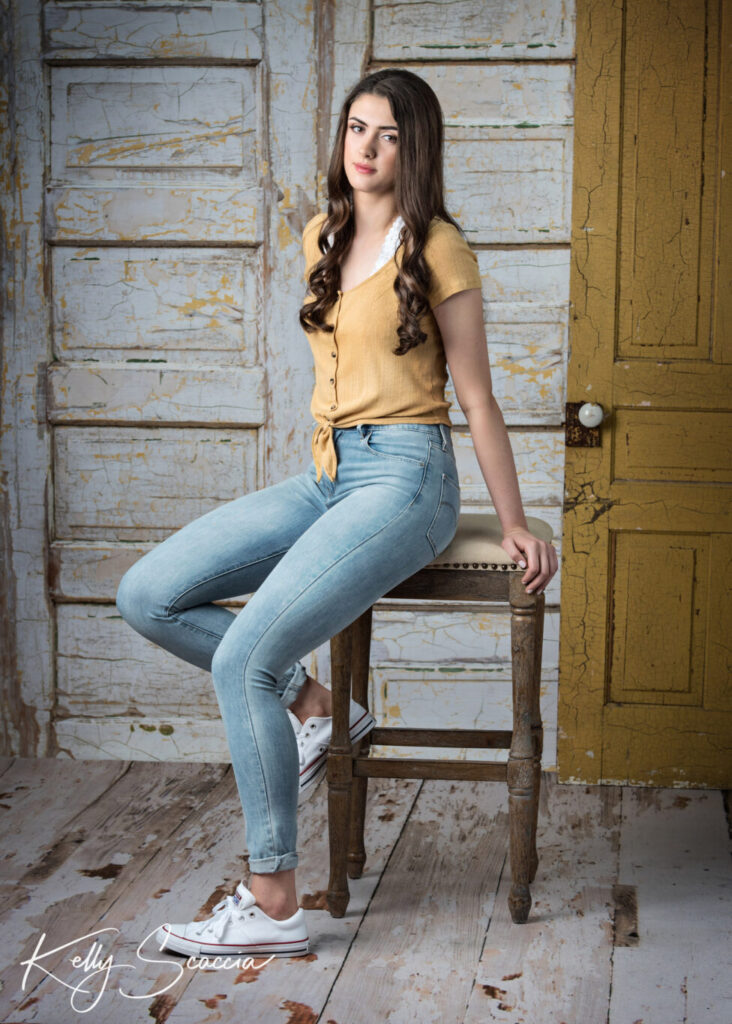 Tall girl with long hair, light jeans, yellow short-sleeve shirt sitting on a tall stool with hands holding the back top while looking straight at you with no smile