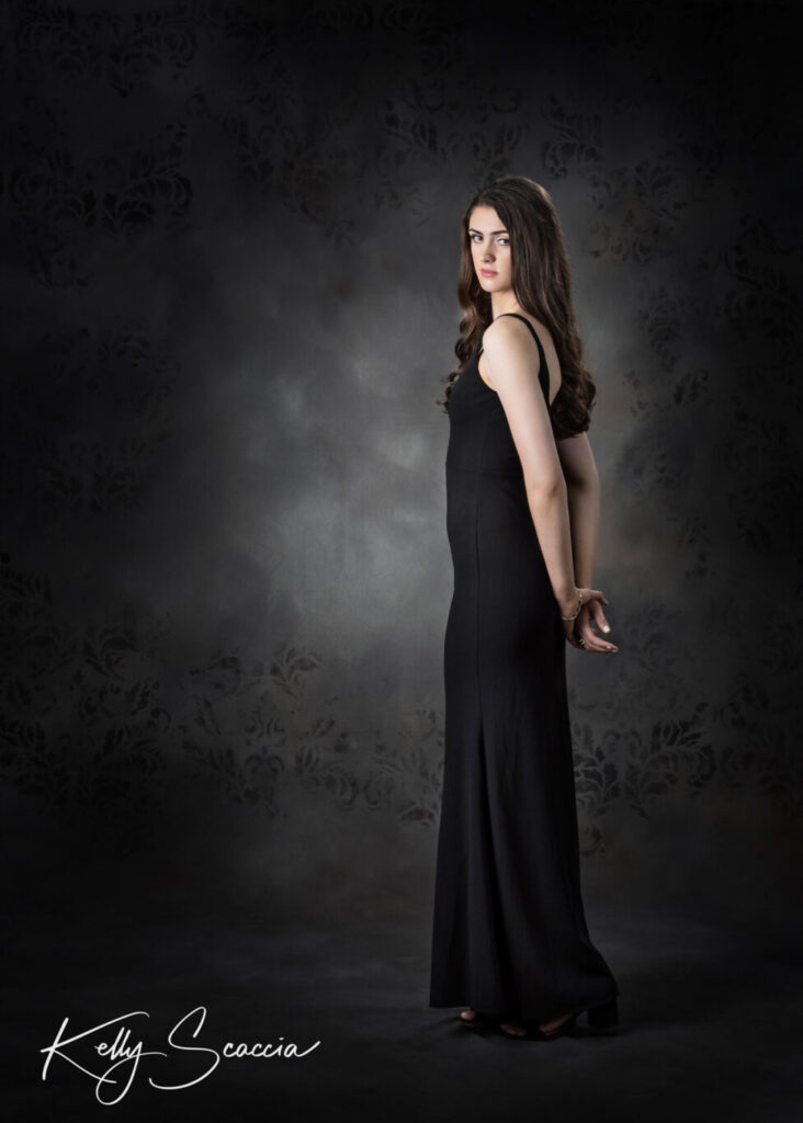 Studio portrait on dark background with tall girl with long dark hair wearing a long fitted sleeveless black dress with arms behind her back staring straight at you with a serious expression