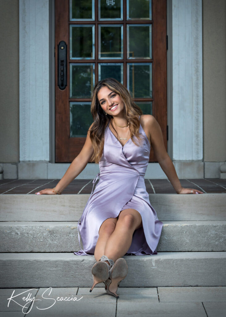 Outdoor senior portrait of a girl with long dark, hair, smiling, sitting on steps in a city wearing a long light purple slip dress with her legs crossed and arms resting behind her