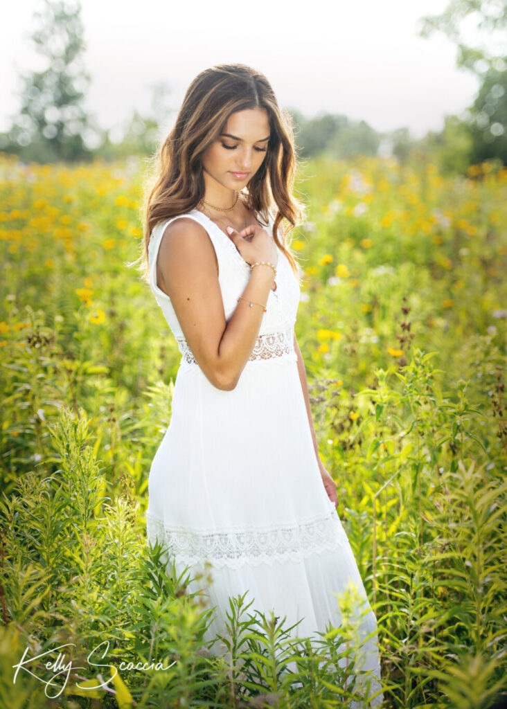 Outdoor senior portrait of a girl with long dark, hair, serious expression wearing a long white dress in a meadow holding her necklace looking down