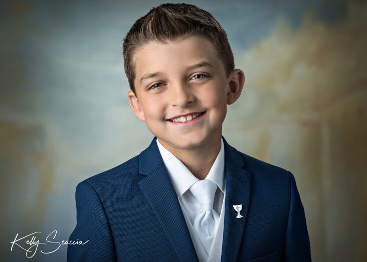 Communion boy in studio on light background head shot looking directly at you smiling