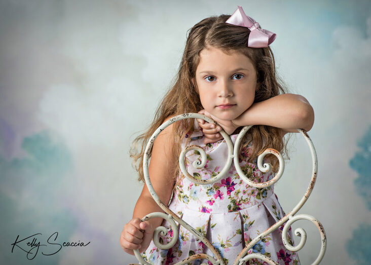 Little girl studio portrait with flowers hand on back of chair looking directly at you no expression
