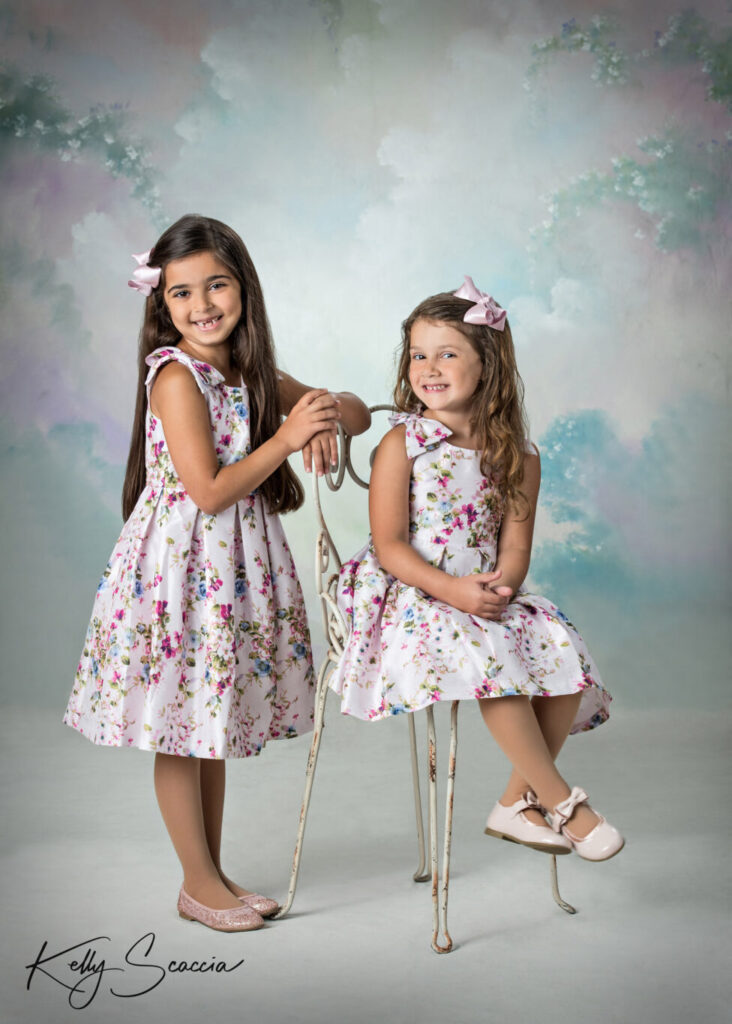 Two little sisters in matching floral dresses in studio on light background smiling and looking at camera