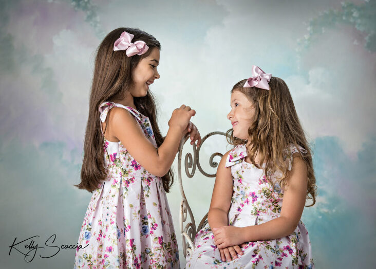 Two little sisters in matching floral dresses in studio on light background smiling and looking at each other