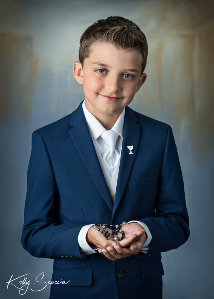 Communion boy in studio on light background with rosary in hands looking directly at you smiling