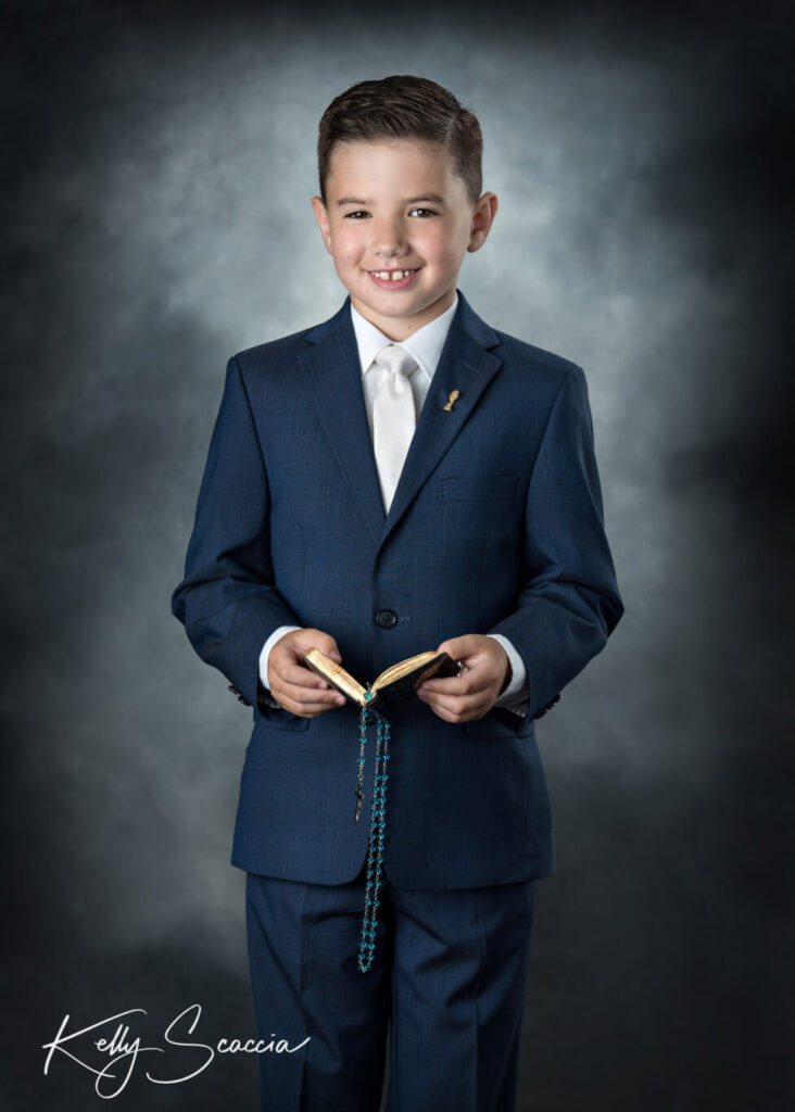 Studio portrait of communion boy in navy suit holding rosary and prayer book looking at you smiling