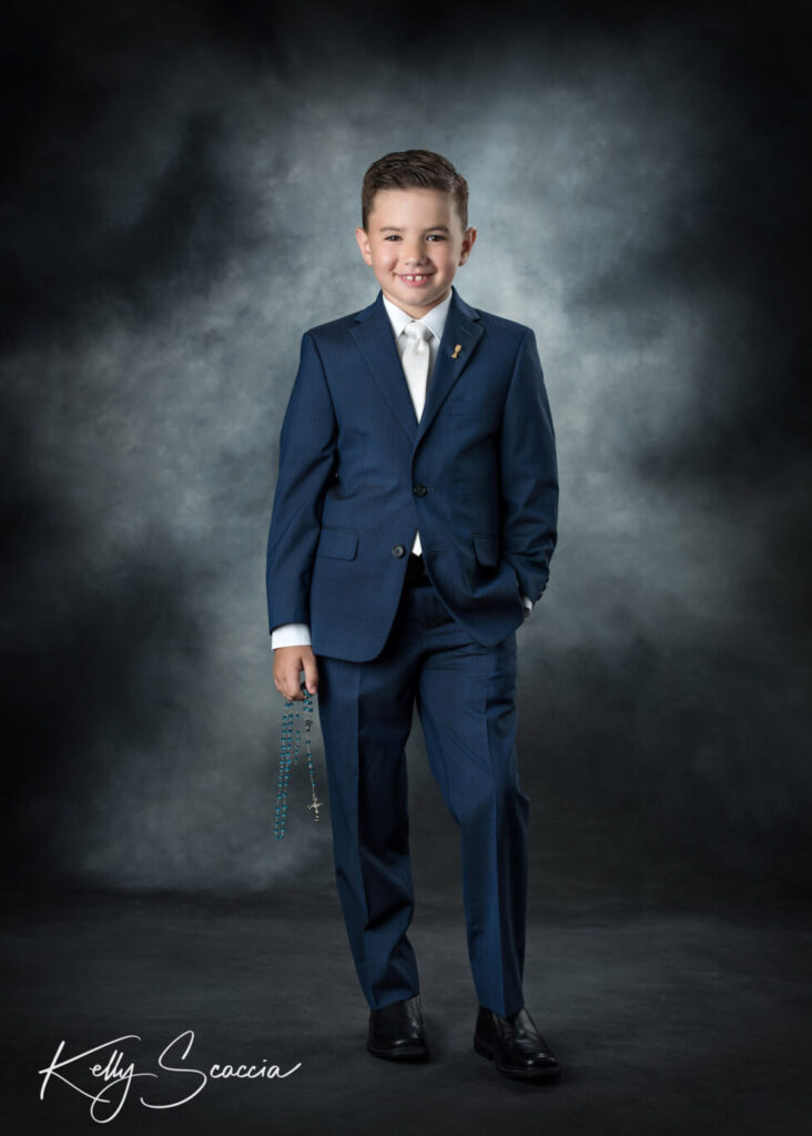 Studio portrait of communion boy in navy suit holding rosary looking at you smiling