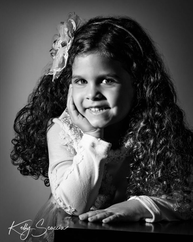 Black and white studio portrait little girl smiling looking at you with one hand resting in front and other hand under her chin