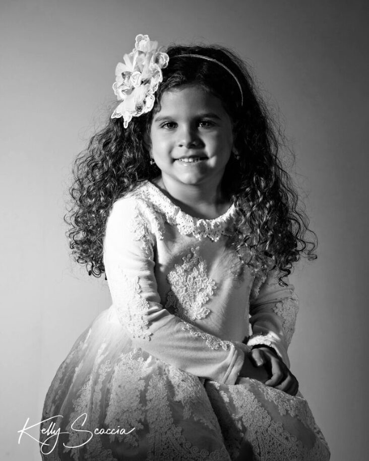 Black and white studio portrait of little girl wearing light dress and headband sitting up looking at you smiling with hands in lap
