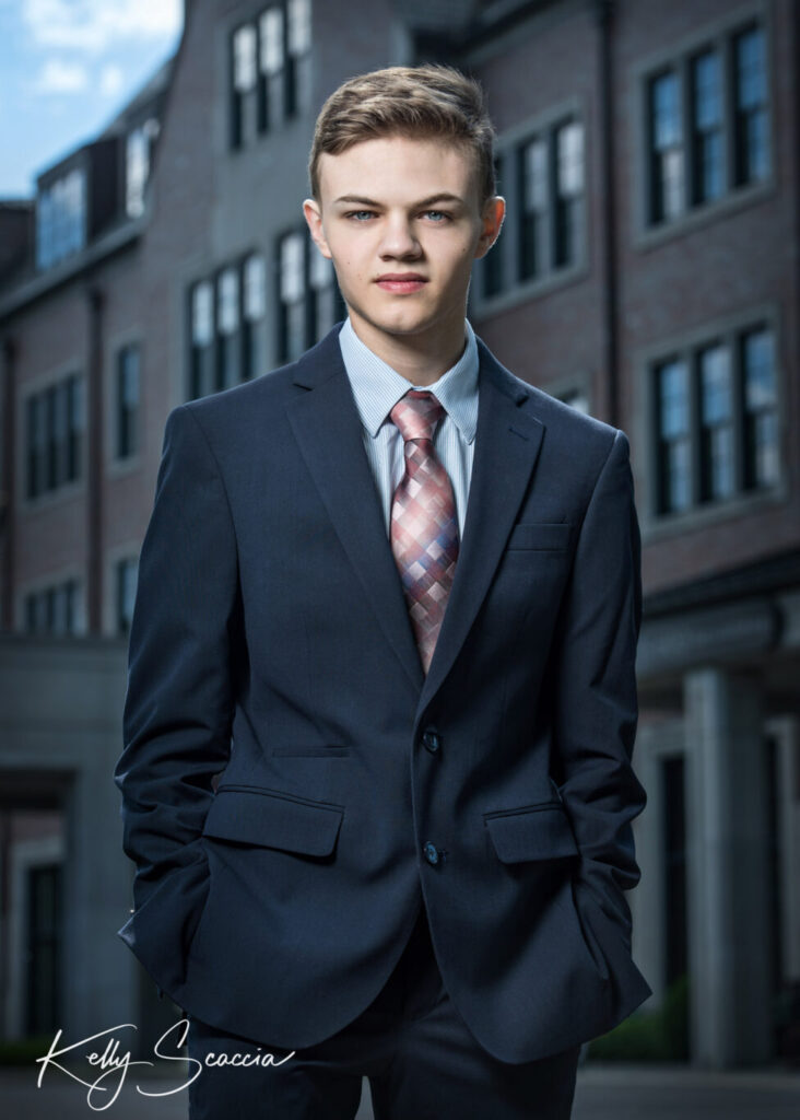 Senior guy portrait wearing a suit looking at you serious expression standing in front of a building with hands in pockets