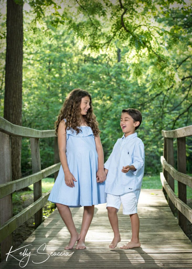 Big sister, little brother outdoor in the park wearing light blue and white holding hands laughing looking at eachother