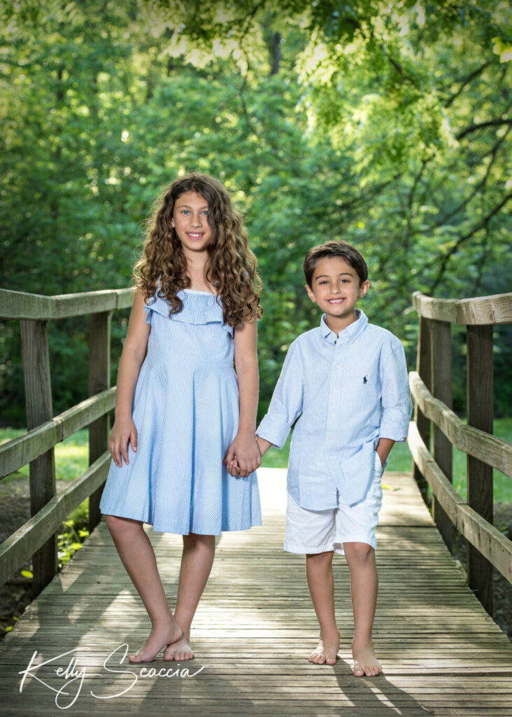 Big sister, little brother outdoor in the park wearing light blue and white holding hands standing on a bridge looking at you smiling