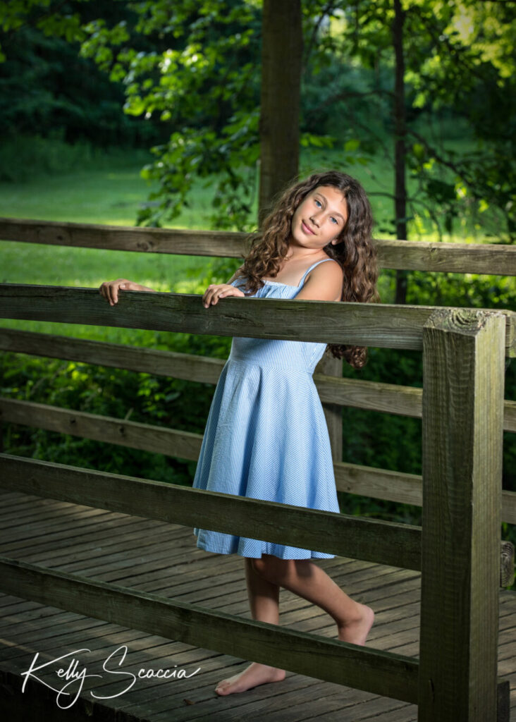 Little girl wearing blue dress in park standing on bridge looking directly at you with hands on rails