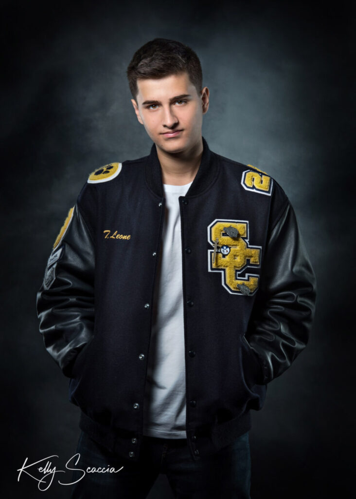 Studio senior guy portrait on dark background looking at you with a serious expression hands in pocket of varsity jacket