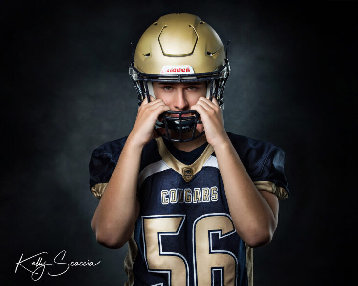 Studio senior guy portrait on dark background looking at you with a serious expression wearing football jersey and jeans wearing gold football helmet with hands on front of it