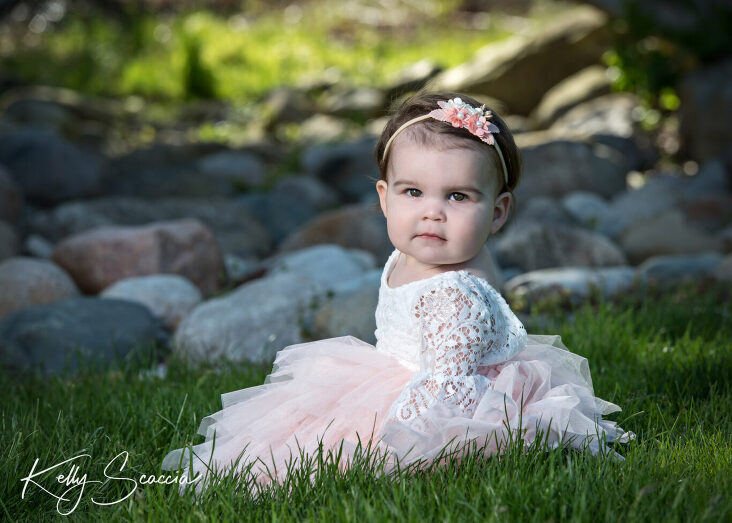 One year baby girl in light pink dress sitting in the grass looking directly at you with a serious face