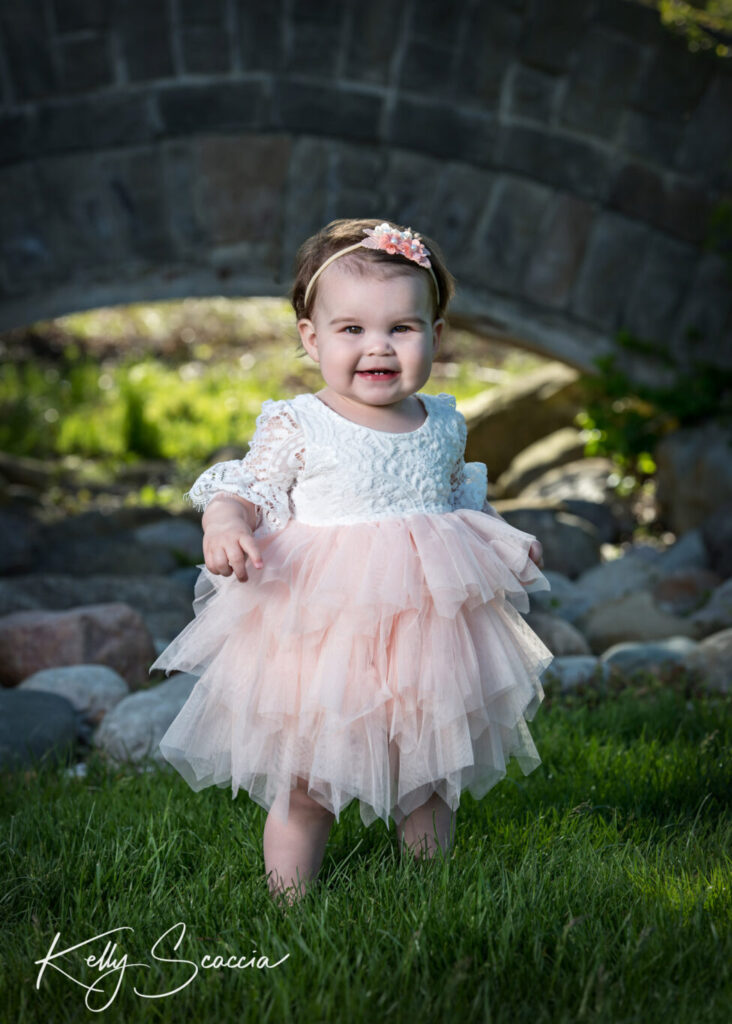 One year baby girl in a pink dress standing in the grass smiling looking directly at you