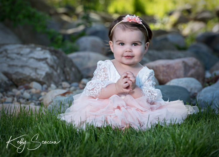 One year baby girl in pink dress sitting in grass holding her hands together looking at you with a smirk
