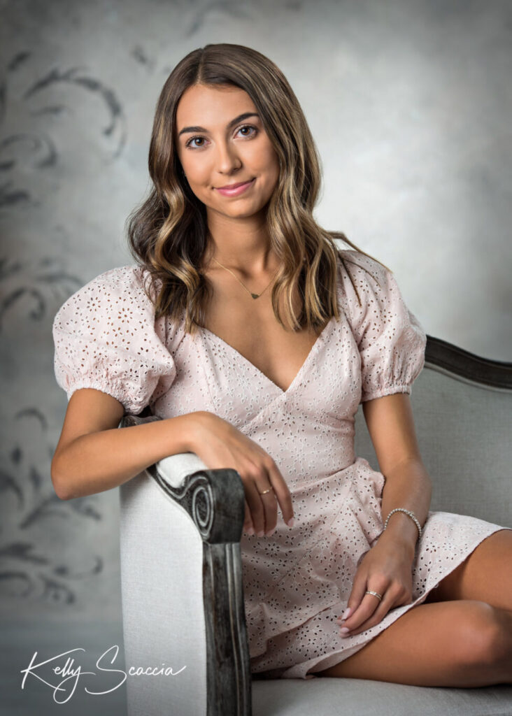 Senior girl studio portrait looking at you smiling wearing pink dress sitting on a white couch