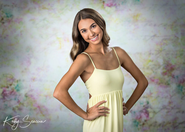 Senior girl studio portrait looking at you smiling wearing yellow dress on a colorful background hands on hips