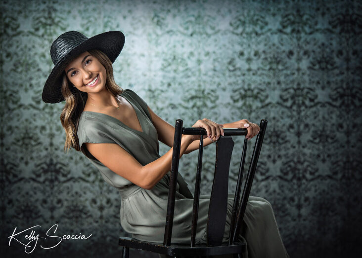 Senior girl studio portrait looking at you smiling wearing green long dress, black hat sitting on a black chair against a black and green background