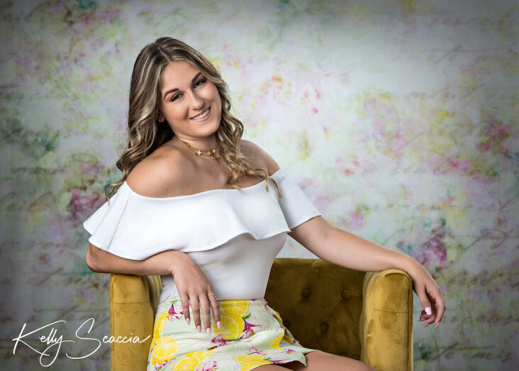 Senior girl studio portrait smiling looking at you wearing a white off the shoulder shirt and yellow floral skirt sitting on a yellow chair