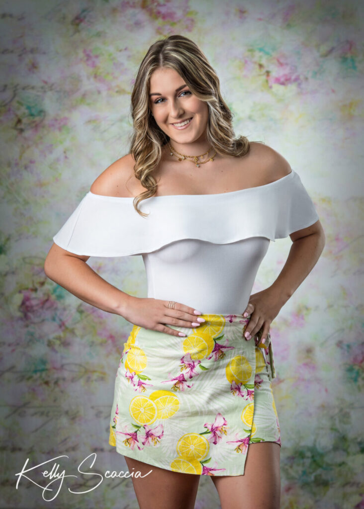 Senior girl studio portrait smiling looking at you wearing a white off the shoulder shirt and yellow floral skirt standing with hands on hips