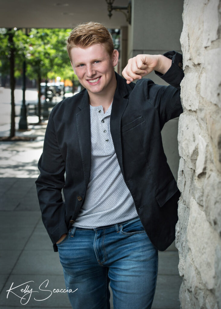 Senior guy outdoor city portrait wearing jeans, gray tshirt, black sport coat smiling looking at you standing in street with right hand in pocket and left hand against the wall