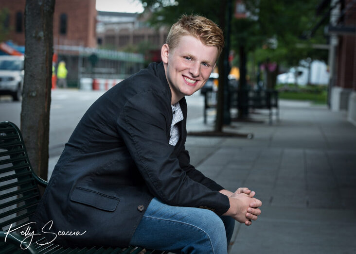 Senior guy outdoor city portrait wearing jeans, gray tshirt, black sport coat smiling looking at you sitting on a bench