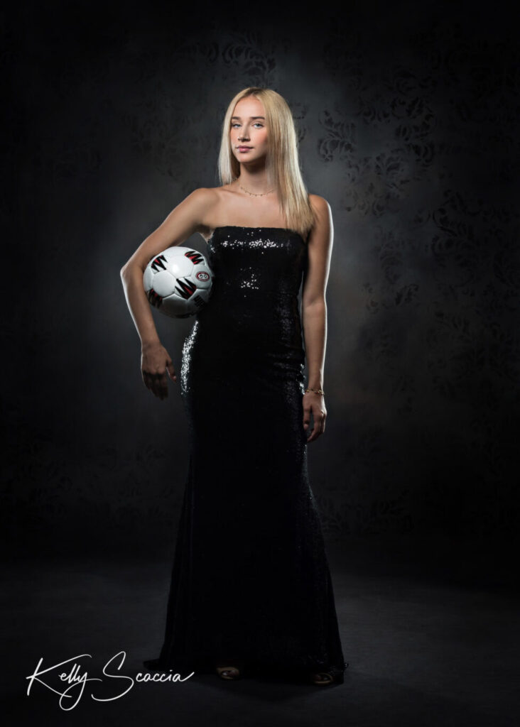 Senior girl studio portrait long dark strapless black sequin dress serious expression standing tall holding soccer ball in crock of right arm looking at you with a serious expression and dramatic lighting