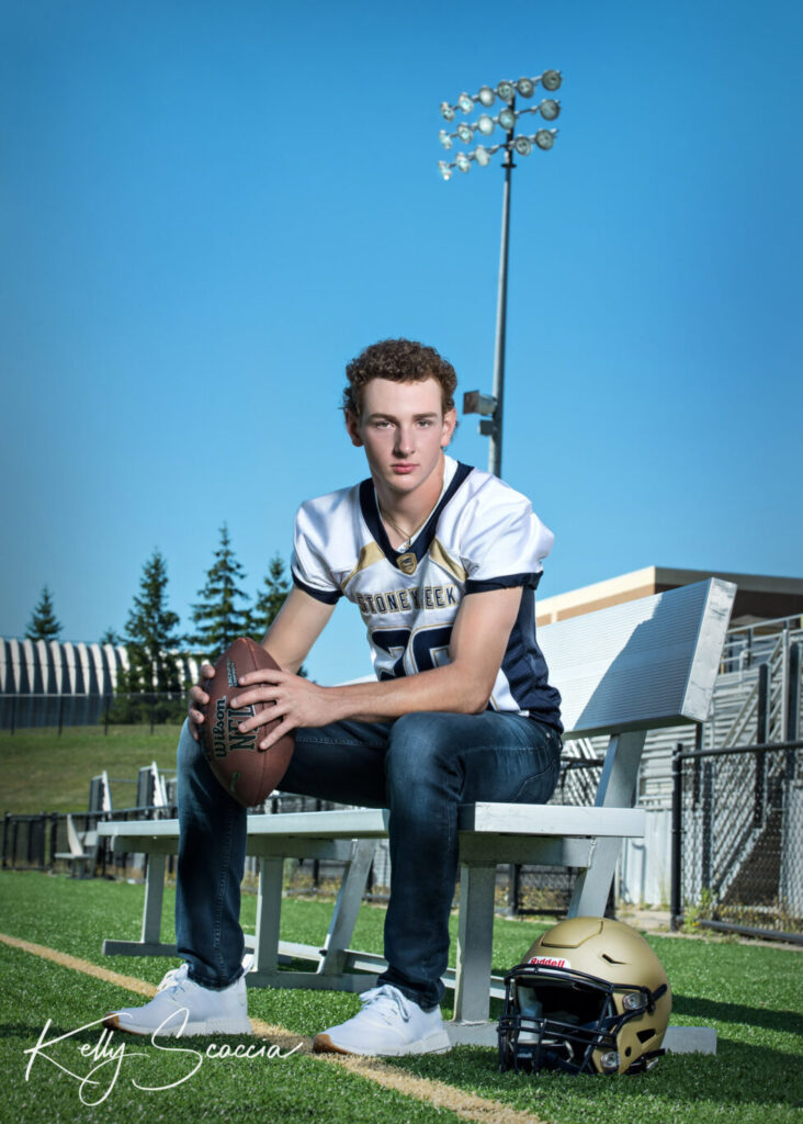 Senior guy outdoor football portrait wearing football jersey and jeans looking at you on the football field sitting on a bench holding the football
