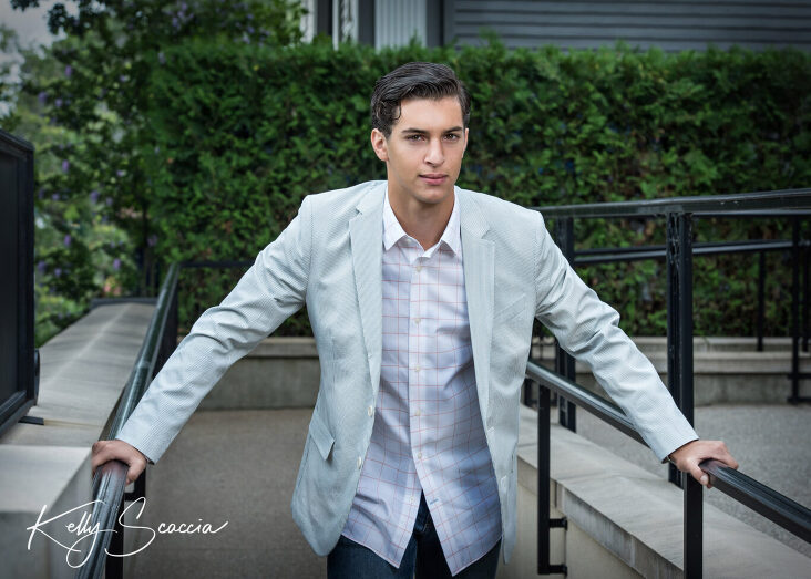 Senior guy outdoor city portrait wearing jeans, white button down and light gray sport jacket looking at you serious expression arms stretch on iron rails on either side of him