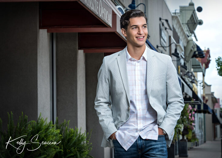 Senior guy outdoor city portrait wearing jeans, white button down and light gray sport jacket looking away smiling with hands in pocket walking on sidewalk in front of storefronts