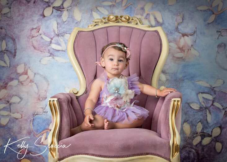 Studio one year little girl portrait in a purple tutu outfit looking at you with a serious expression sitting on a purple chair