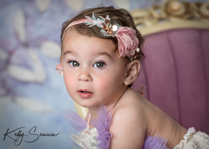 Studio one year little girl portrait in a purple tutu outfit looking at you with a serious expression sitting on a purple chair headshot