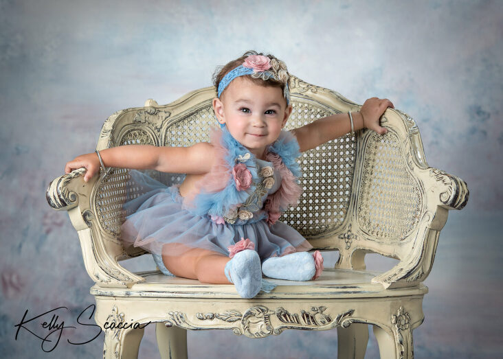 One year girl studio portrait wearing pink and blue tutu dress looking at you sitting on a cream chair