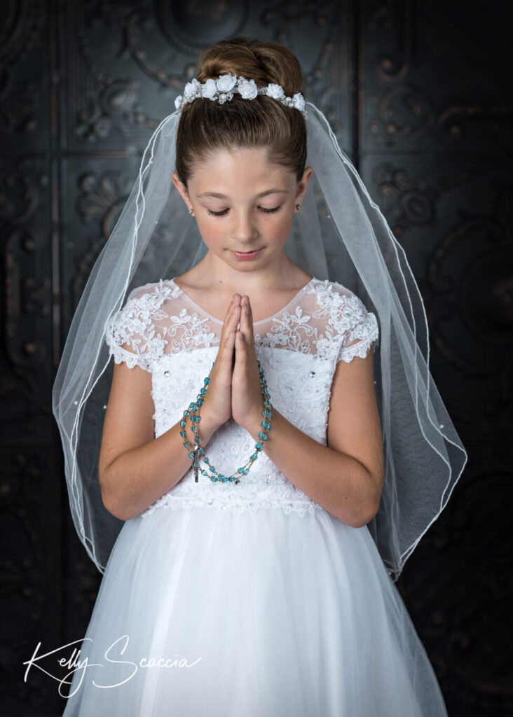Studio communion girl portrait wearing a white communion dress wearing a tiara her rosary draped across her hands with a serious expression on her face hands in prayer looking down at them