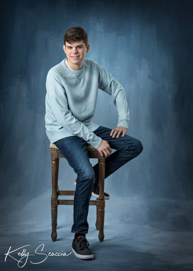 Senior guy studio portrait dark, short hair  wearing jeans and light blue long sleeve sweater looking directly at you no smile