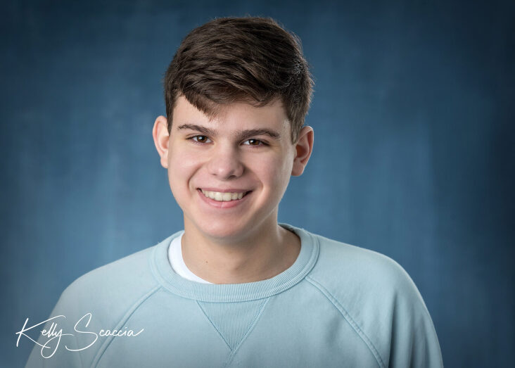 Senior guy studio portrait headshot dark, short hair wearing a light blue long sleeve sweater looking directly at you smiling