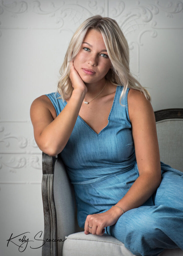 Senior girl studio portrait blonde hair blue eyes wearing denim jumpsuit sitting on white couch with right hand under chin looking at you with a serious expression