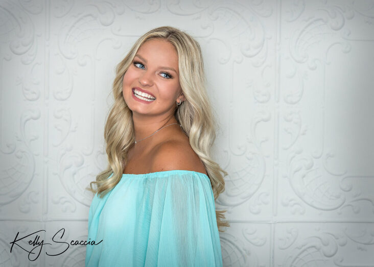 Senior girl studio portrait long blonde hair, blue eyes smiling looking away from you wearing a light seaform off the shoulder romper