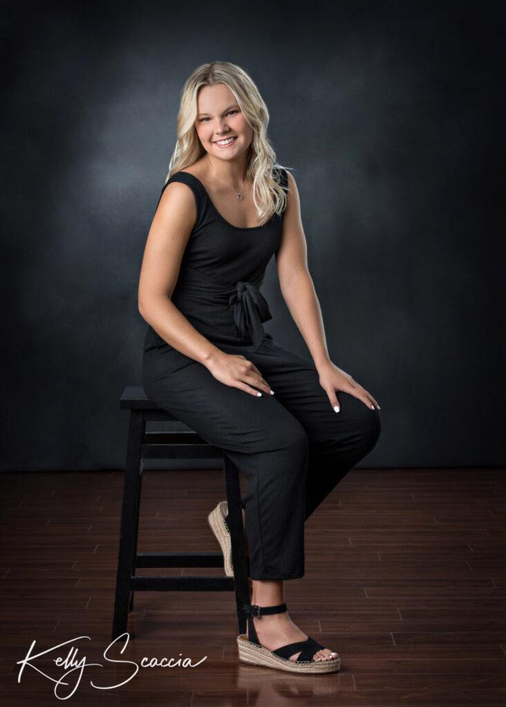 Studio senior girl portrait looking at you, smiling, sitting wearing long, black pantsuit