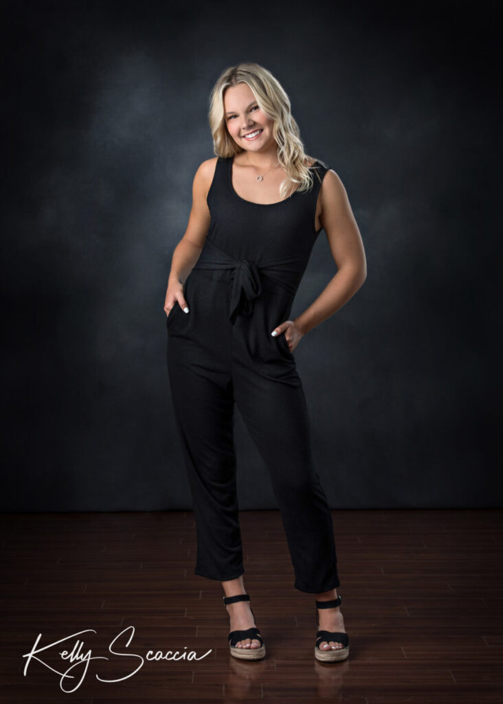 Studio senior girl portrait looking at you, smiling, standing wearing long, black pantsuit