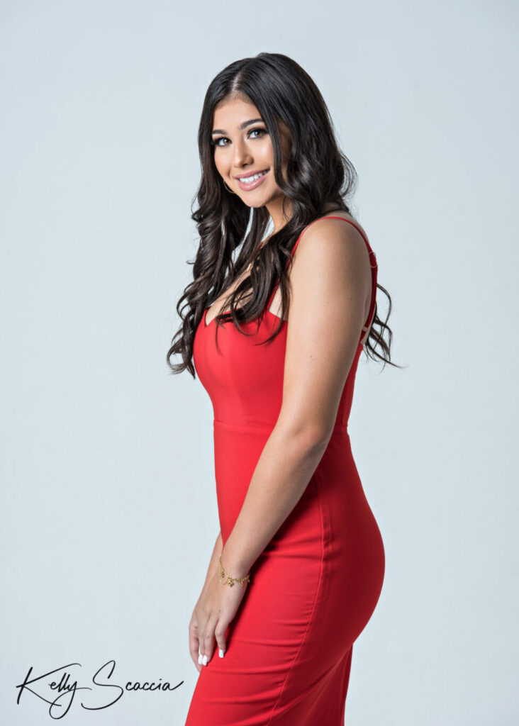 Senior girl studio portrait on a light background wearing a red dress smiling looking at you