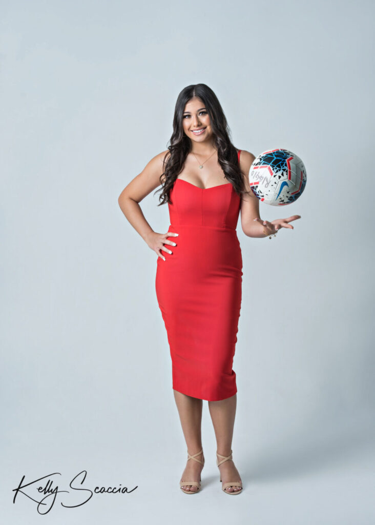 Studio senior girl portrait holding soccer ball in her hand wearing a red dress looking at you smiling