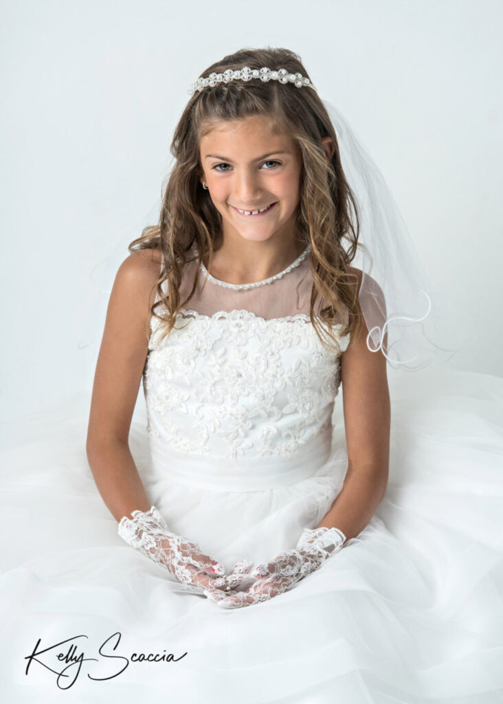 First Holy Communion girl studio portrait on a light background wearing a white dress, veil looking at smiling